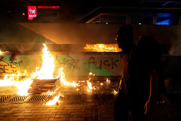 An anti-government protester is seen next to a fire at the Sham Shui Po Station, during a demonstration on China's National Day in Hong Kong