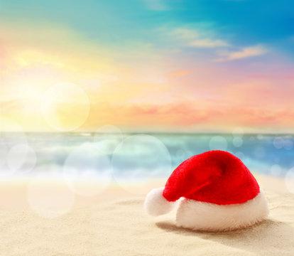 Christmas holidays concept. Santa claus hat on summer sand beach
