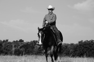 Western lifestyle image in black and white of cowboy riding horse through Texas field.