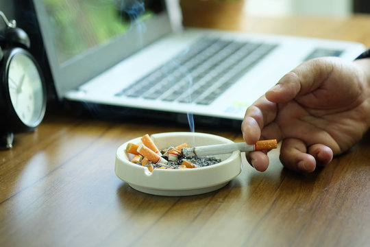 Many cigarette in white ashtray on the desk with laptop computer. Smoking to relieve stress at work but unhealthy