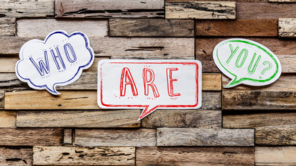 Speech bubbles on wooden background : who are you ?