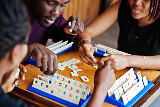 Group of three african american friends play table games.