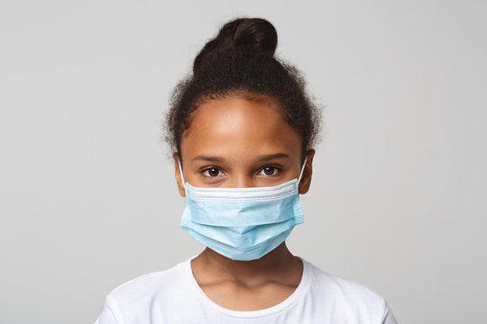 Portrait of little black girl wearing medical mask