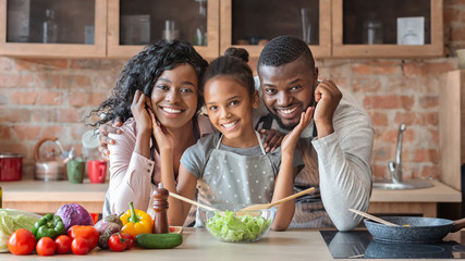 Lovely family cooking healthy dinner together at kitchen