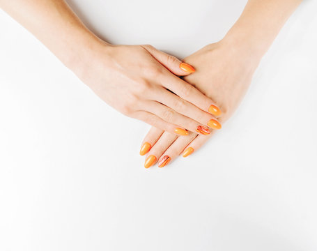 Female hands with professional manicure of orange color.