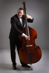 Portrait of a man with a double bass on a gray background. Musician with a big double bass.