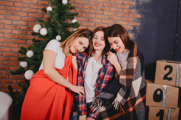 Three beautiful girls in a photo studio. Women near Christmas tree. Ladies in a white t-shirts