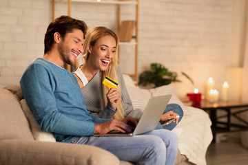 Happy Spouses Using Laptop And Online Shopping Card At Home