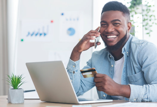 Cheerful black guy talking on phone and holding credit card