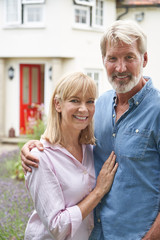 Portrait Of Mature Couple Standing In Garden In Front Of Dream Home In Countryside