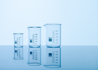 Three empty measuring beakers sitting on a mirror blue surface