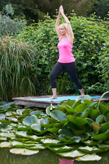 Mature Woman In Yoga Position On Wooden Jetty By Lake