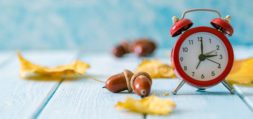 Autumn time change concept - red alarm clock on wood background, copy space