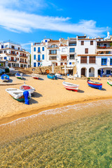 Fishing boats on beach in Port Bo with colorful houses of old town of Calella de Palafrugell in background, Catalonia, Spain