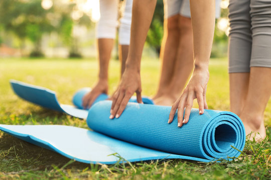 People rolling up yoga mat in park at morning, closeup