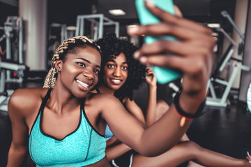 Two beautiful girls in the gym do selfie. Sports, fitness, boxing, gym.