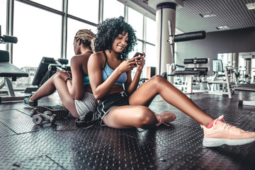 Group of sporty female friends using smartphone at gym. Fototapete