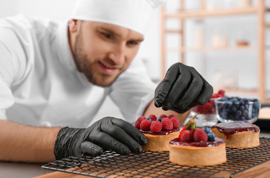 Male pastry chef preparing desserts at table in kitchen