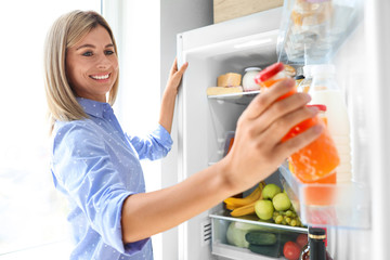 Woman taking bottle with juice out of refrigerator in kitchen