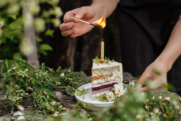 Girl's hands light a candle on a piece of cake
