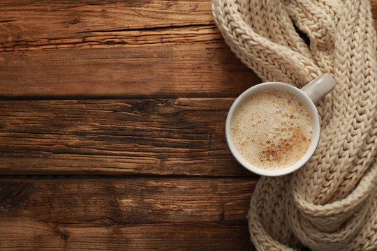Top view of coffee and knitted scarf on wooden table, space for text. Cozy winter