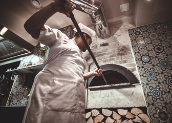 Experienced chef is putting his pizza to the oven using special giant spatula. Wall mural