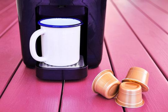 Espresso cappuccino machine, capsules and a vintage mug on a pink wooden table