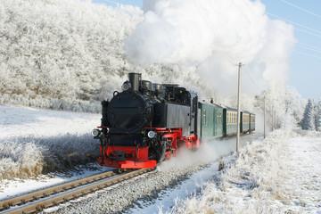 dampflok vor personenzug im winter mit viel dampf