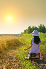 Rear view of girl with sunflowers, sitting on american flag suitcase, looking at sunset in golden wheat field
