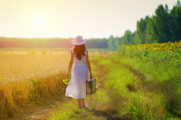 Rear view of walking young woman with sunflowers and suitcase with field      American flag on it in golden wheat