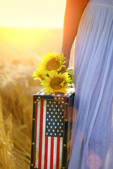 Woman in golden wheat field holding suitcase with american flag and sunflowers.Sunset, unrecognizable woman, part of body