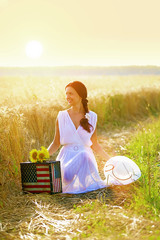 Beautiful young woman with american flag suitcase and sunflowers sitting in golden wheat field, looking away.Sunset light