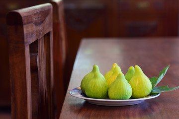 Scene in a country kitchen in Sicily with rustic wooden furniture and a plate of fresh green figs on the table