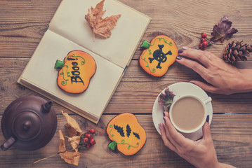 Halloween cookies and cup of coffee on the table. Women's hands, a cup of coffee, a book, Halloween postcard, toned image