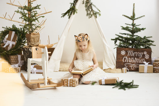 A portrait of a little girl near the wigwam and Christmas tree unpacking Christmas gifts on a white background