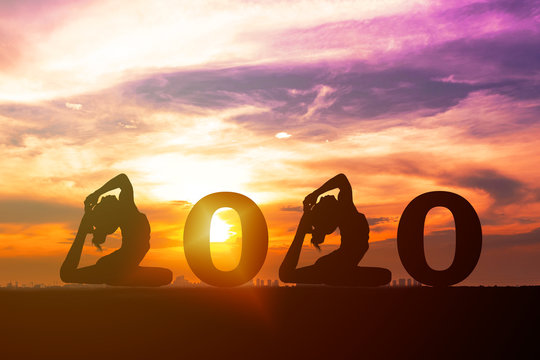Greeting card 2020 happy new years. Silhouette of healthy young woman practicing yoga and 2020 years with sky sunset. People doing yoga standing between numbers 2020. concept celebrating new year.