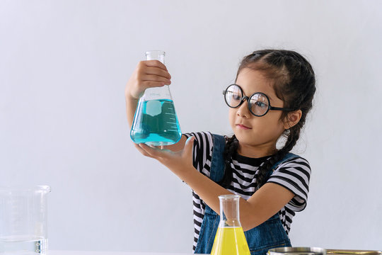 Little 6s cute girl with microscope holding laboratory bottle with water experiment study scientists at school. Education science concept.