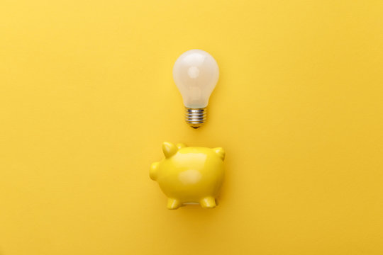 top view of piggy bank with light bulb on yellow background
