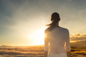 Life is beautiful. Woman standing facing a beautiful golden sunrise.