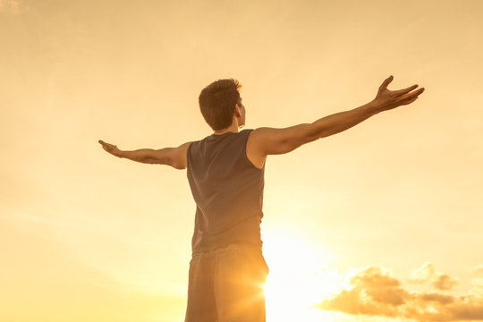 Success achievement accomplishment and motivation concept with man sunset silhouette celebrating arms up raised outstretched outdoors in nature