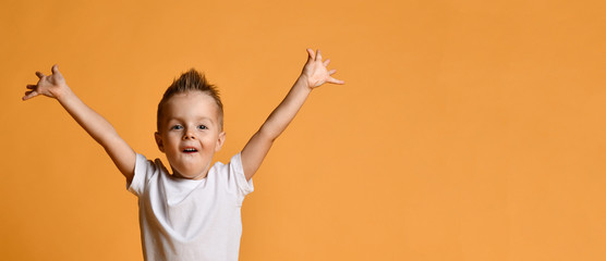 Young boy kid in white t-shirt celebrating happy smiling laughing with hands spreading up on yellow Wall mural