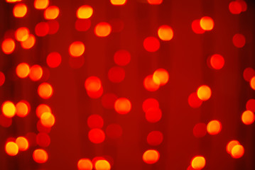 Red-orange trendy festive background of blurry Christmas lights