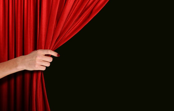 Hand opening red curtain over black background