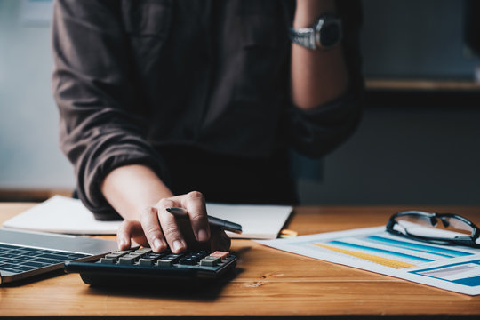Business woman entrepreneur using a calculator with a pen in her hand, calculating financial expense.