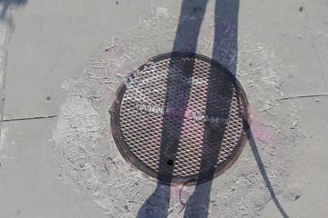 Woman's legs shadow with dog leash on manhole cover city street