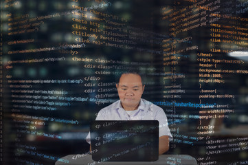 A focused IT student writing codes for building websites and a burst of codes surrounding the web designer. Focus and concentrated man with a little enthusiasm in his job. Working at midnight.