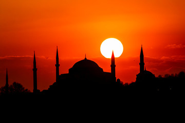 Cityscape of Istanbul with silhouettes of ancient mosques and minarets at sunset. Panoramic view, The Maiden's Tower, Galata Tower, Hagia Sophia, The Blue Mosque and Topkapı Palace in Istanbul.