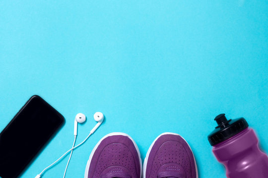 headphones, sneakers, water bottle and phone on blue background flat lay