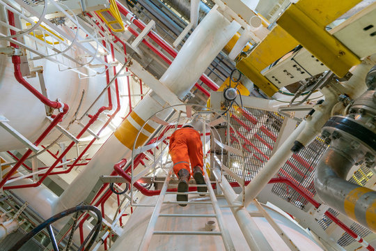 Production operator working at offshore oil and gas central processing platform for inspect and observe gas treatment process.