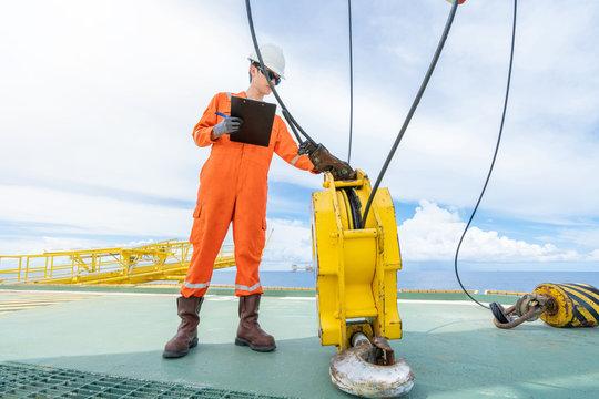 Crane inspector inspection lifting equipment of offshore oil and gas platform pedestal crane for preventive maintenance.
